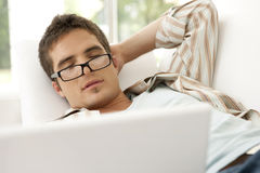 Diríjase la tecnología dormida en el sofá con la computadora portátil Foto de archivo libre de regalías