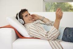 Diríjase la tecnología en el sofá que escucha los auriculares Imágenes de archivo libres de regalías