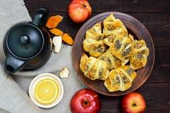 Diríjase los panecillos hechos de los cruasanes con las manzanas, adornadas con las semillas de amapola en un cuenco de la arcill Imágenes de archivo libres de regalías