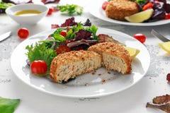 Diríjase los salmones, la espinaca y la patata hechos de la croqueta de pescados servido en la placa con las verduras Foto de archivo