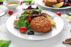 Diríjase los salmones, la espinaca y la patata hechos de la croqueta de pescados servido en la placa con las verduras Imagen de archivo
