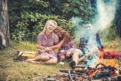 Dire gli scherzi dal falò Amici di risata che si accampano in legno Fumo di fuoco di accampamento che copre la gente fotografia stock libera da diritti