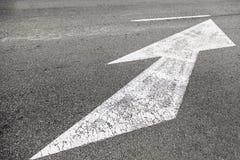 Dirección de la flecha en el asfalto Fotografía de archivo