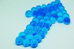 Dirección punteaguda de la flecha, alineada con las bolas de cristal azules Foto de archivo