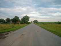 Direct asphalt road through the countryside under the sky, on which the clouds float royalty free stock photo