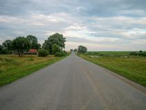 Direct asphalt road through the countryside under the sky, on which the clouds float stock photos