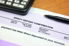 Direct Deposit Confirmation. A direct deposit confirmation notice on a desk with a calculator and a pen Stock Photography