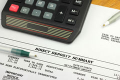 Direct Deposit Summary. A calculator and two pens rest on top of a bank statement showing the electronic transmittal of funds Stock Photo