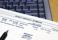 Direct Deposit Summary and Laptop. A banking document showing the electronic transmittal of funds with a laptop computer keyboard Royalty Free Stock Images