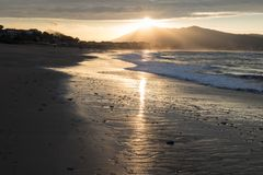 Direct golden sunset`s sunlight on a scenic sandy beach in hendaye in dramatic cloudy atmosphere, basque country, france. Direct golden sunset`s sunlight on a royalty free stock photography