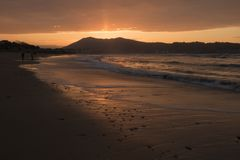 Direct golden sunset`s sunlight on a scenic sandy beach in hendaye in dramatic cloudy atmosphere, basque country, france. Direct golden sunset`s sunlight on a royalty free stock images