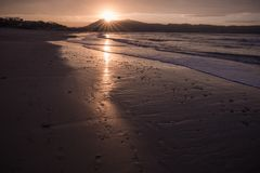 Direct golden sunset`s sunlight on a scenic sandy beach in hendaye in dramatic cloudy atmosphere, basque country, france. Direct golden sunset`s sunlight on a stock image