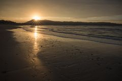 Direct golden sunset`s sunlight on a scenic sandy beach in hendaye in dramatic cloudy atmosphere, basque country, france. Direct golden sunset`s sunlight on a stock photos