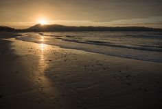 Direct golden sunset`s sunlight on a scenic sandy beach in hendaye in dramatic cloudy atmosphere, basque country, france. Direct golden sunset`s sunlight on a royalty free stock image