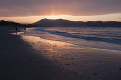 Direct golden sunset`s sunlight on a scenic sandy beach in hendaye in dramatic cloudy atmosphere, basque country, france. Direct golden sunset`s sunlight on a royalty free stock photo