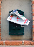 Direct mail. Advertising brochures in green metalic mailbox. Wall mailbox Stock Photos