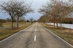 Direct road to the fields in the countryside. Direct asphalt road among fields in the countryside stock image