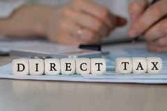 Words DIRECT TAX composed of wooden letters. DIRECT TAX composed of wooden dices. Closeup royalty free stock photo