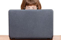 Direct view of girl with glasses reads from laptop Stock Photography