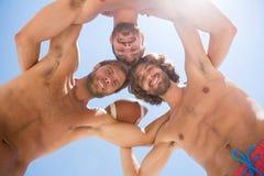 Directement au-dessous du portrait des amis masculins se blottissant tout en jouant le football américain Image stock