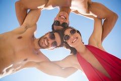 Directement au-dessous du tir de jeunes amis de sourire se blottissant contre le ciel bleu clair Photos stock