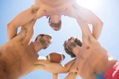 Directement au-dessous du tir des amis masculins se blottissant tout en jouant le football américain Photo stock