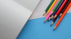 Directement au-dessus du tir des crayons colorés par des livres sur le fond bleu photographie stock