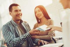 Directeur à l'agence de voyages donnant des billets aux couples image stock