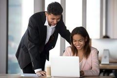 Directeur arabe de sourire dirigeant le nouveau travailleur africain aider avec l'ordinateur portable photographie stock