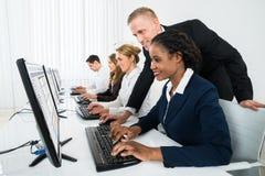 Directeur Assisting His Staff dans le bureau image libre de droits