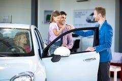 Directeur commercial à une voiture de salle d'exposition avec des acheteurs Photo libre de droits