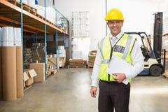 Directeur d'entrepôt utilisant le casque antichoc tenant le presse-papiers Image stock