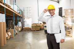 Directeur d'entrepôt utilisant le casque antichoc tenant le presse-papiers Images stock