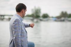 Directeur d'entreprise attendant sur un fond brouillé de ville Homme d'affaires avec une montre blanc de réussite d'isolement par Images libres de droits