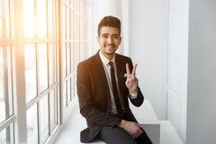 Directeur d'entreprise réussi s'asseyant sur le rebord de fenêtre Images libres de droits