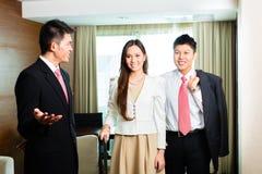 Directeur d'hôtel chinois asiatique présent la suite photos libres de droits