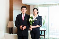 Directeur d'hôtel chinois asiatique souhaitant la bienvenue à des invités de VIP photographie stock