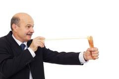 Directeur dans un costume jouant le tir avec la fronde images libres de droits