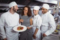 Directeur de restaurant agissant l'un sur l'autre avec son personnel de cuisine Image libre de droits