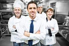 Directeur de restaurant posant devant l'équipe de chefs photos stock