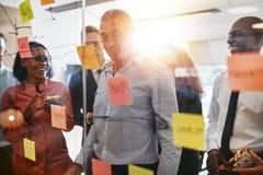 Directeur de sourire faisant un brainstorm avec son équipe dans un bureau images libres de droits