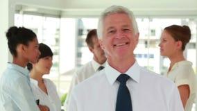 Directeur de sourire posant avec ses employés à l'arrière-plan banque de vidéos