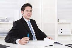 Directeur de sourire s'asseyant au bureau - succès. photographie stock libre de droits