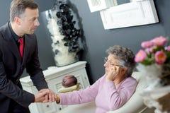 Directeur des pompes funèbres tenant la dame de personnes âgées de main photo libre de droits
