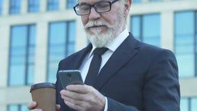 Directeur die cellphone gebruiken om bedrijf van afstand, geschikte technologie te controleren stock video