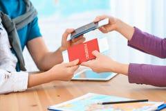 Directeur féminin donnant des passeports avec des billets aux clients à l'agence de voyages photographie stock
