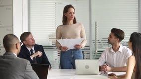 Directeur féminin tenant des papiers parlant aux employés recueillis à se réunir clips vidéos