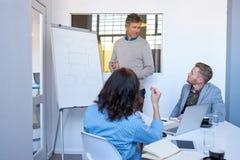 Directeur faisant une présentation aux collègues de bureau sur un tableau blanc Photo stock