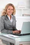 Directeur femelle heureux à son bureau Images libres de droits
