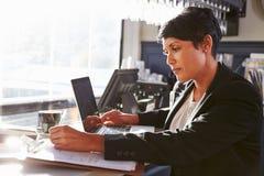 Directeur féminin de restaurant travaillant au compteur Images stock